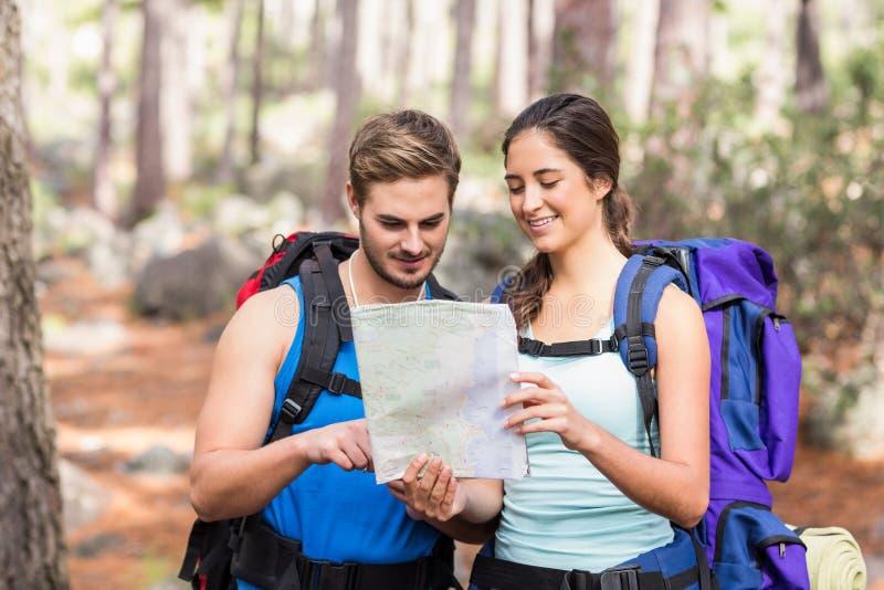 Glückliche Wanderer, die Karte betrachten stockfotografie