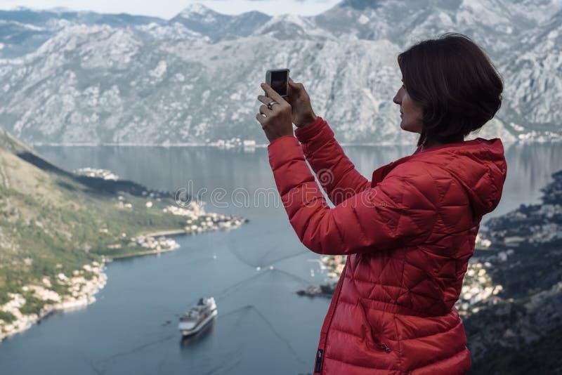 Glückliche Wandererfrau, die Smartphonephotos am szenischen Standpunkt macht stockbild