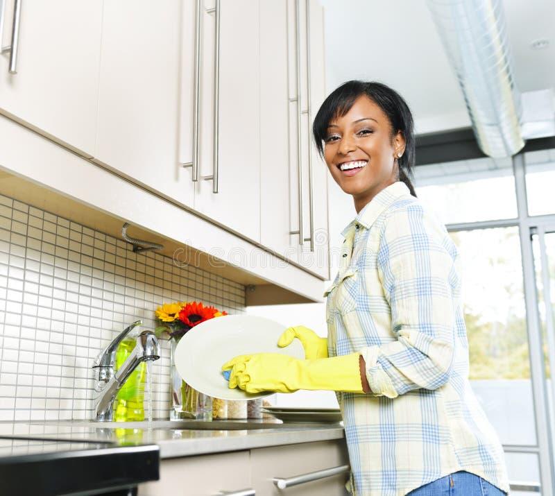 Glückliche waschende Teller der jungen Frau stockfoto