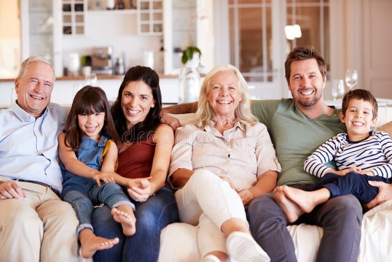 Glückliche weiße Familie mit drei Generationen, die auf einem Sofa zusammen zu Hause lächelnd zur Kamera, Vorderansicht sitzt stockbild