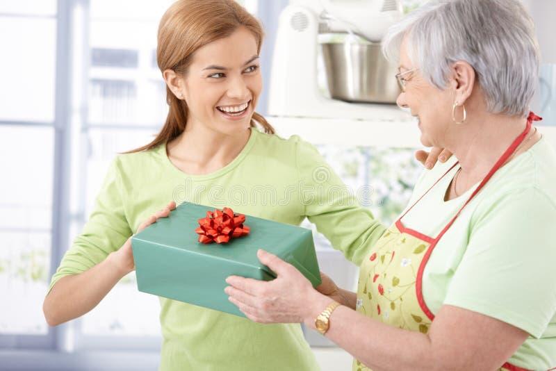 Glückliche weibliche darstellende Mutter mit Geschenk lizenzfreie stockbilder