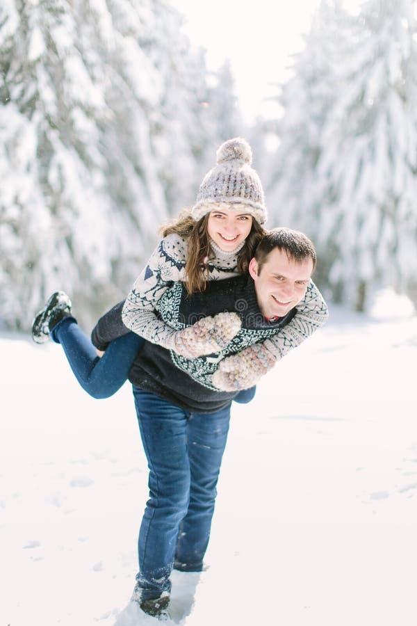 Glückliche Winterreisenpaare Mann, der Frauendoppelpolfahrt auf Winterferien im schneebedeckten Wald gibt stockfotos