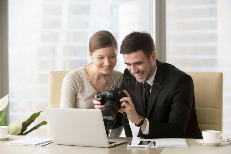 Glückliche Wirtschaftler, die Bilder vom Fotoschießen auf PR aufpassen stockfotos