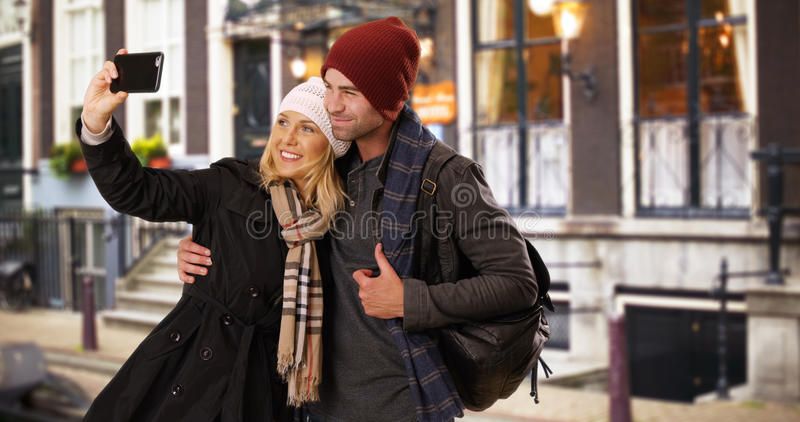Glückliche yuccie Paare, die draußen ein selfie in der Stadt nehmen stockbild