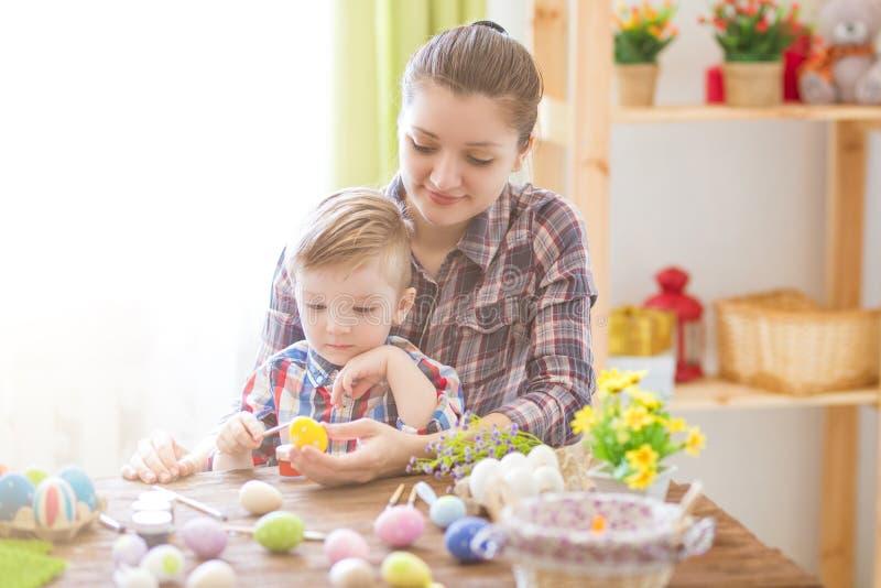 Glückliche Zeit beim Malen von Ostereiern Junges Küken in Wanne, 2 malte Eier und Blumen Glückliche Mutter und ihr nettes Kind, d stockfotografie
