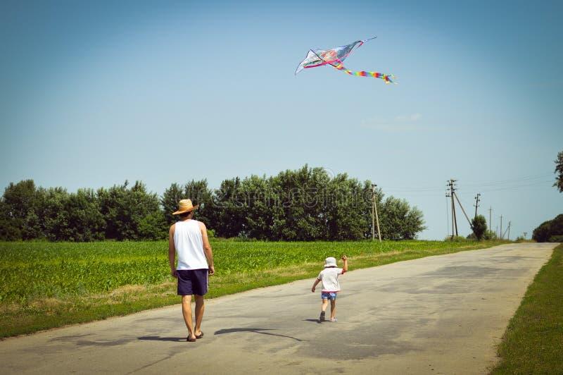 Glückliche Zeiten: Bild des Vaters u. des Sohns, die den Spaß draußen spielt mit Drachen auf Grünholz des Sommers sonniger Tagesu lizenzfreie stockbilder
