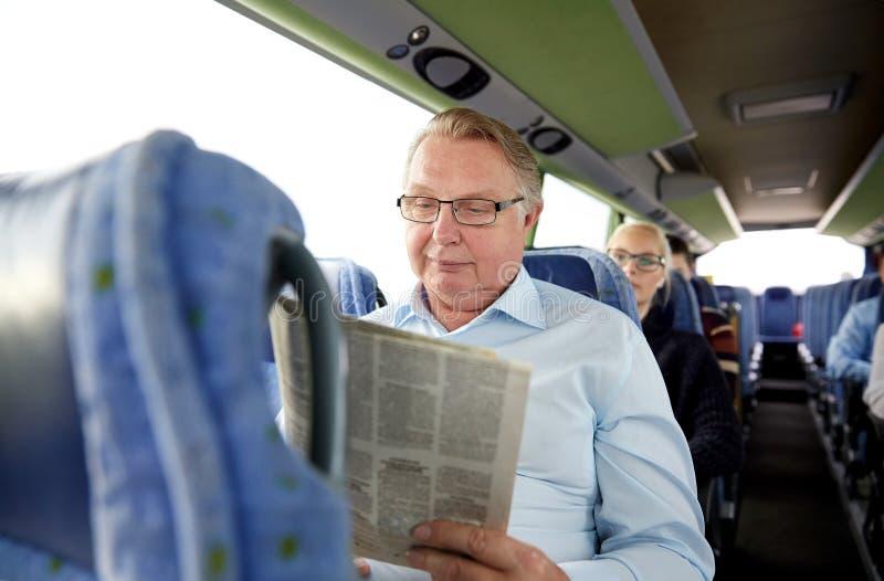 Glückliche Zeitung des älteren Mannes Leseim Reisebus stockfotografie