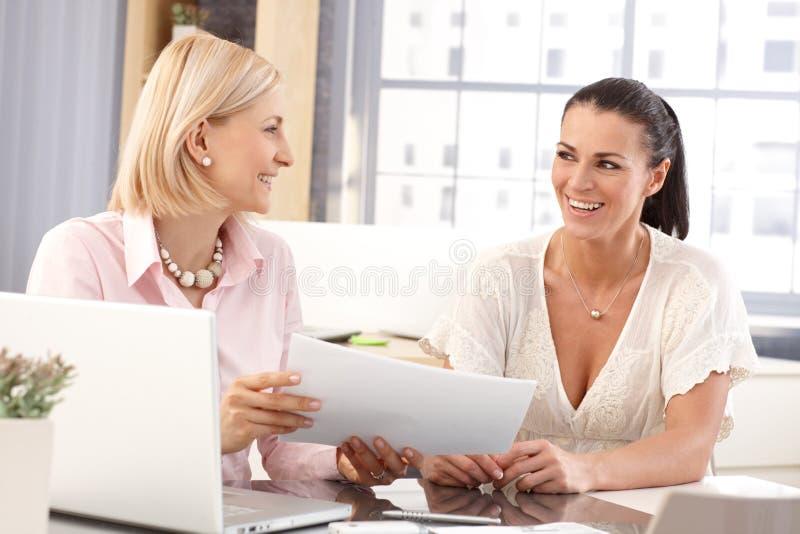 Glückliche zufällige Geschäftsfrauen an der Bürofunktion stockfotos