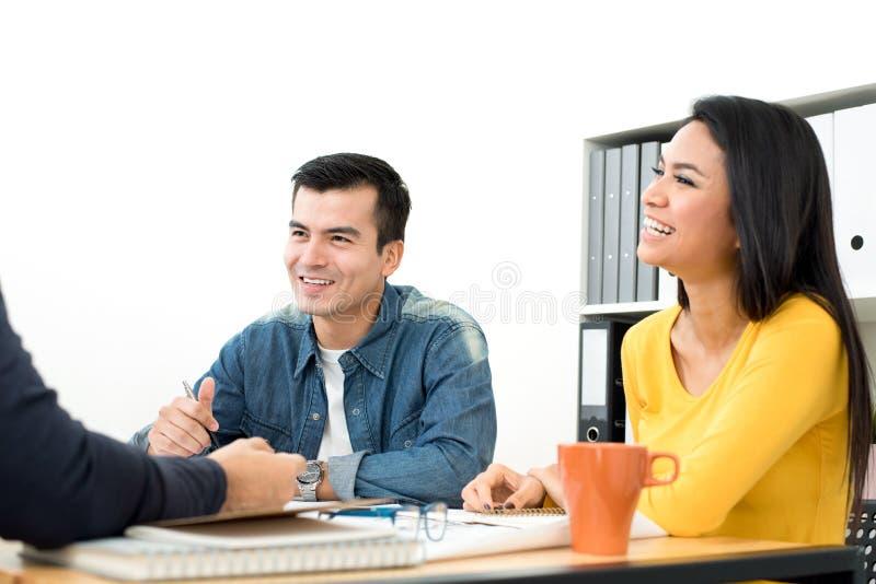 Glückliche zufällige Geschäftsleute, die in der Sitzung lachen und lächeln stockfoto