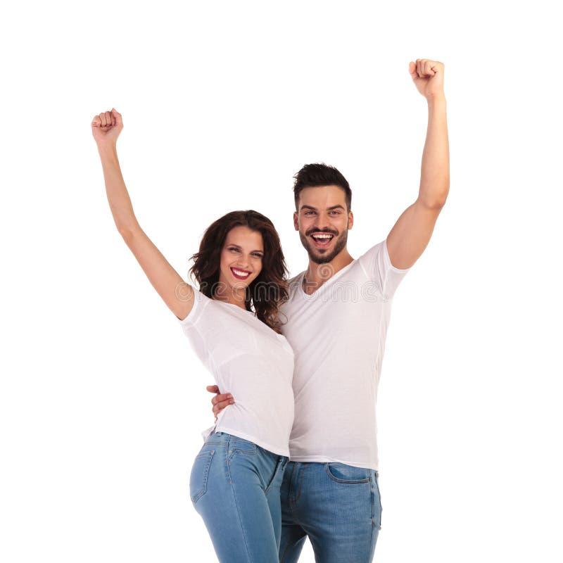 Glückliche zufällige Paare, die Erfolg mit den Händen in der Luft feiern stockfotografie