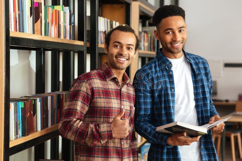 Glückliche zwei afrikanische Mannstudenten, die in den Bibliothekslesebüchern stehen lizenzfreie stockbilder