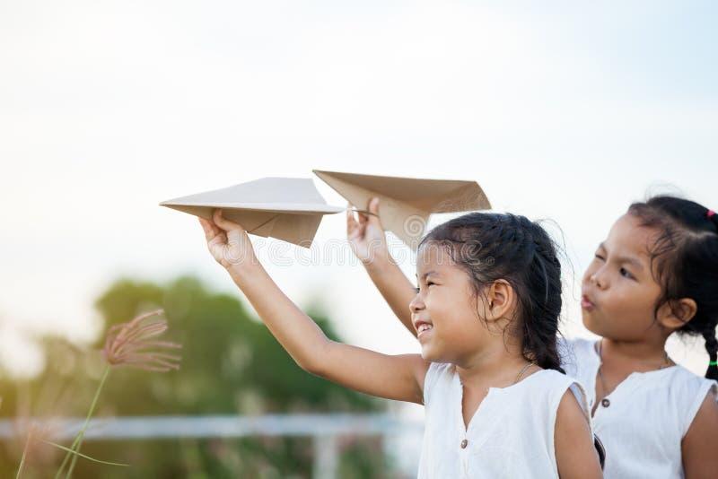 Glückliche zwei asiatische Kindermädchen, die mit Spielzeugpapierflugzeug spielen stockbilder