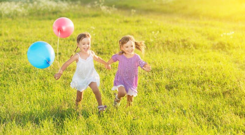 Glückliche Zwillingsschwestern, die um das Lachen und das Spielen mit Ballonen im Sommer laufen stockfotos
