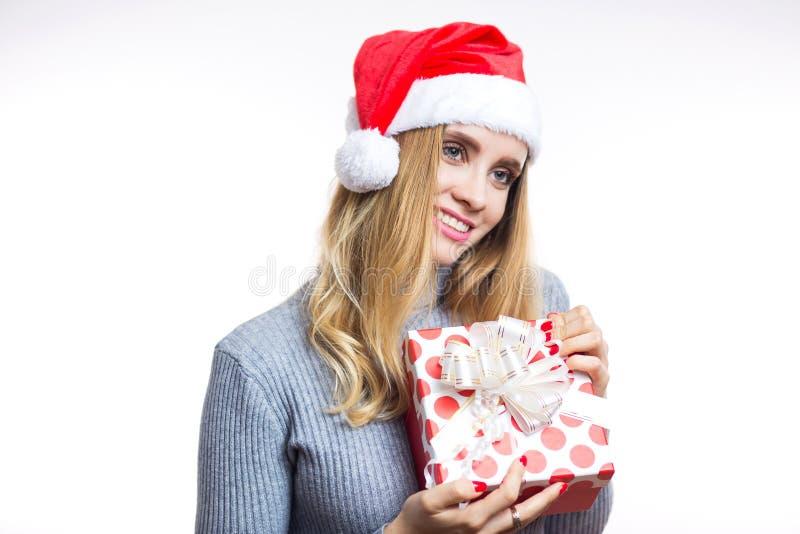 Glücklichen jungen Blondine in einer grauen Strickjacke und Sankt roten einem Hut empfingen ein Geschenk für Weihnachten, neues J stockfoto