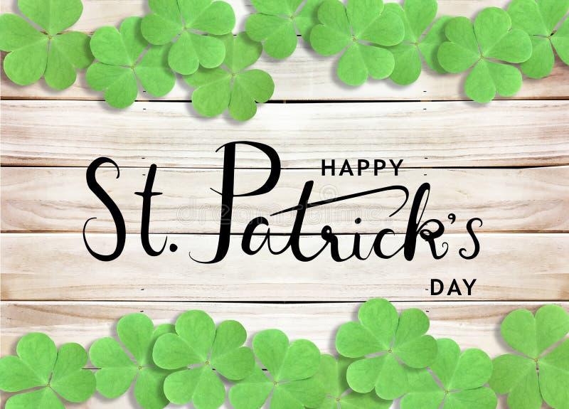 Glücklichen St Patrick Tagesschwarz-Text-Typografie-Hintergrund mit grünen Shamrocks auf hölzerner Beschaffenheit lizenzfreie stockfotos