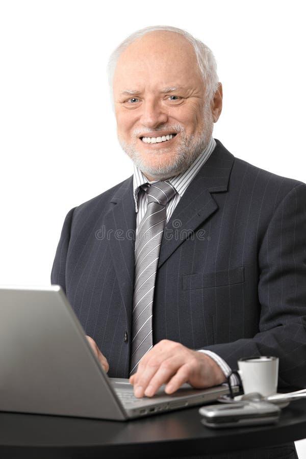 Glücklicher älterer Geschäftsmann unter Verwendung des Computers lizenzfreies stockbild