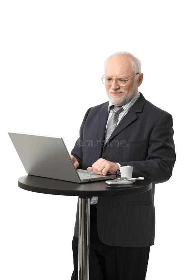Glücklicher älterer Geschäftsmann unter Verwendung des Computers stockfotografie