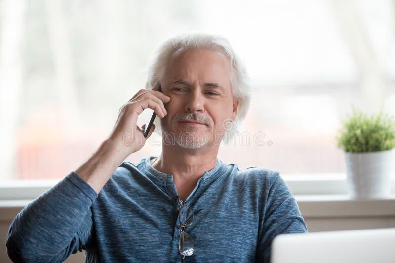 Glücklicher älterer Mann, der angenehmes Mobiltelefongespräch hat stockbilder