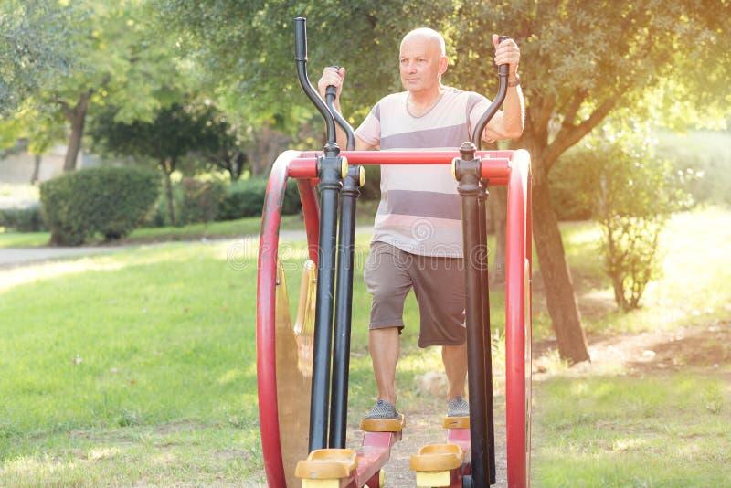 Glücklicher älterer Mann, der auf der allgemeinen Ausrüstung des Sports in der Turnhalle im Freien ausarbeitet Sportiver Mann, de stockbild