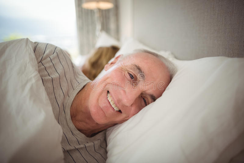 Glücklicher älterer Mann, der auf Bett liegt stockfotografie