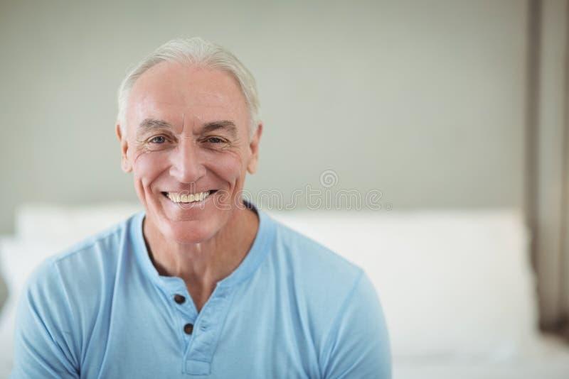 Glücklicher älterer Mann, der auf Bett sitzt lizenzfreies stockbild
