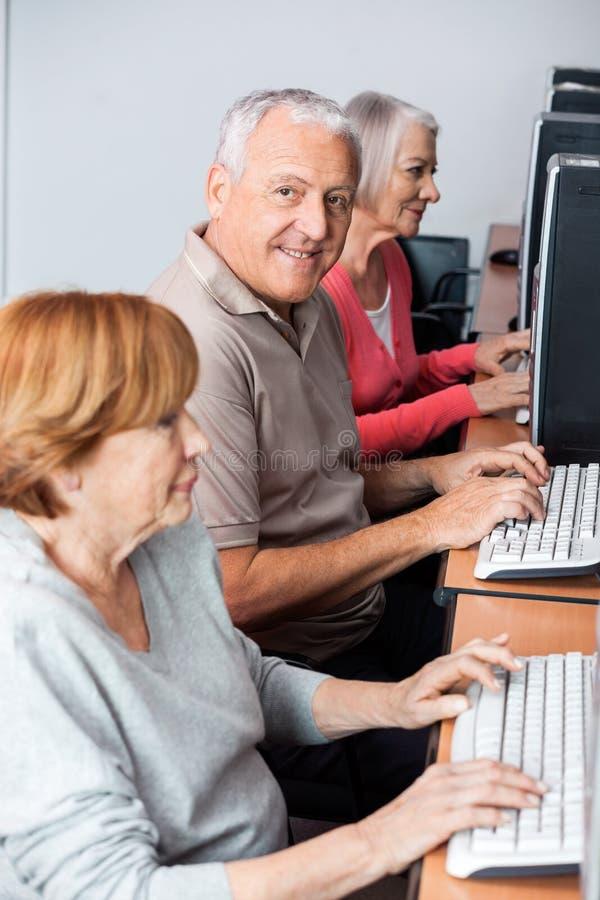 Glücklicher älterer Mann, der Computer im Klassenzimmer verwendet lizenzfreie stockbilder