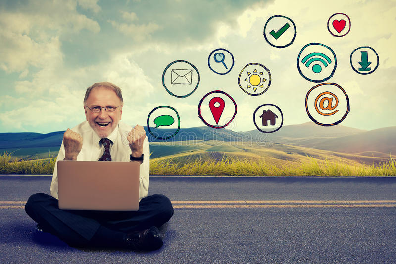 Glücklicher älterer Mann, der an Computer unter Verwendung der Social Media-Anwendung arbeitet stockbilder