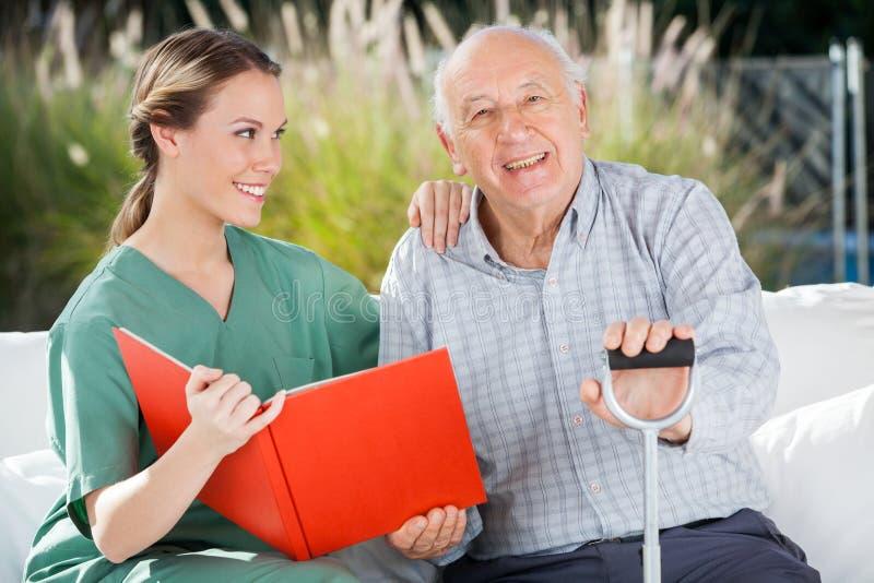 Glücklicher älterer Mann, der durch weibliche Krankenschwester Holding sitzt lizenzfreies stockfoto