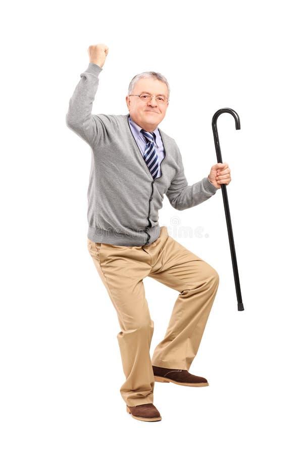 Glücklicher älterer Mann, der einen Stock anhält und Glück gestikuliert stockbild