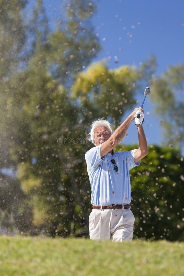 Glücklicher älterer Mann, der Golfball aus einem Bunker heraus spielt stockbild