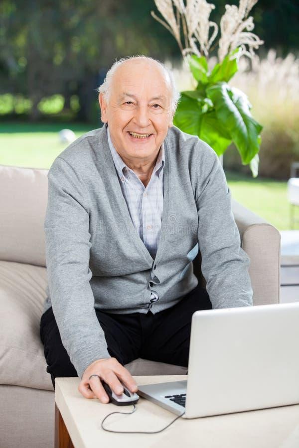 Glücklicher älterer Mann, der Laptop am Pflegeheim verwendet stockbilder