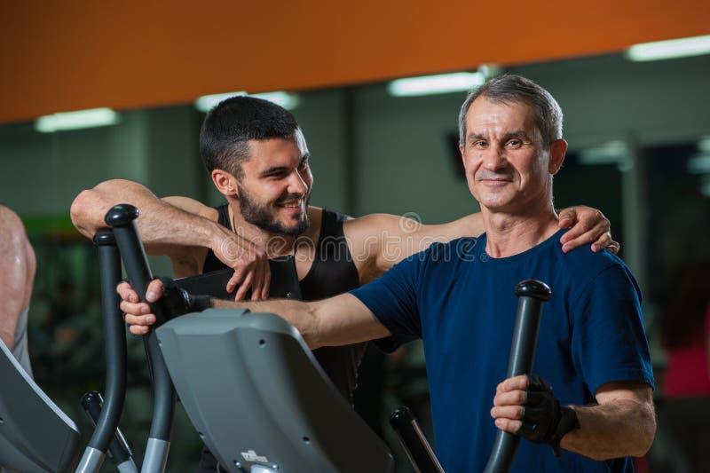 Glücklicher älterer Mann, der mit persönlichem Trainer arbeitet lizenzfreies stockbild