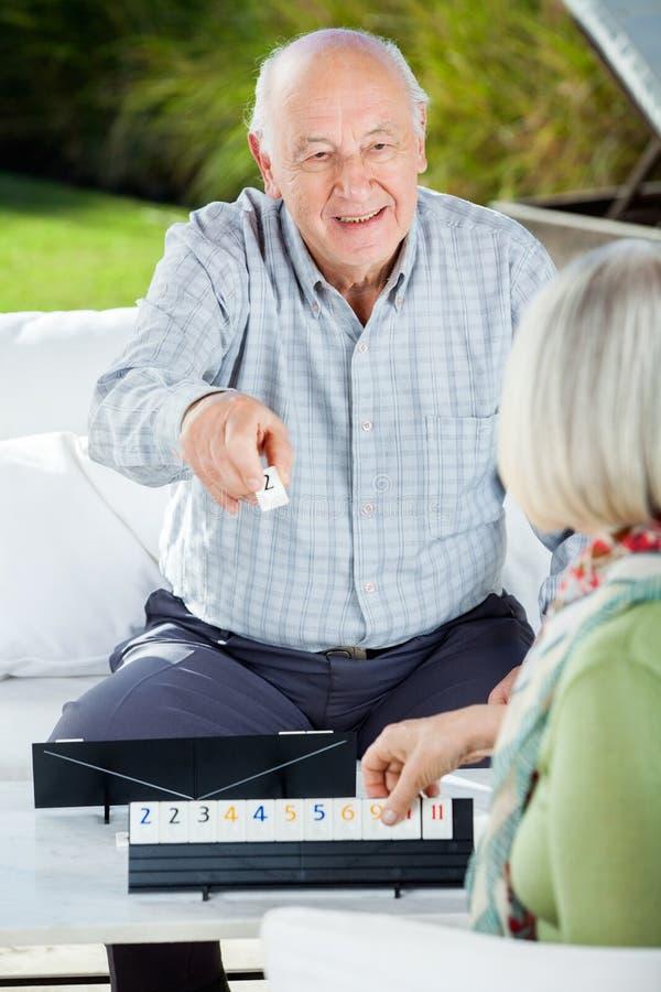 Glücklicher älterer Mann, der Rummy With Woman spielt stockfotos