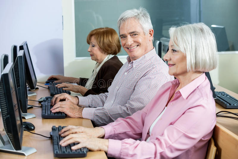 Glücklicher älterer Mann, der am Schreibtisch in der Computer-Klasse sitzt lizenzfreies stockbild