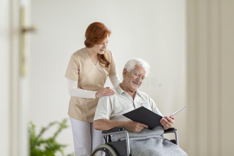 Glücklicher älterer Mann im Rollstuhl ein Buch während des Besuchs lesend stockfotos