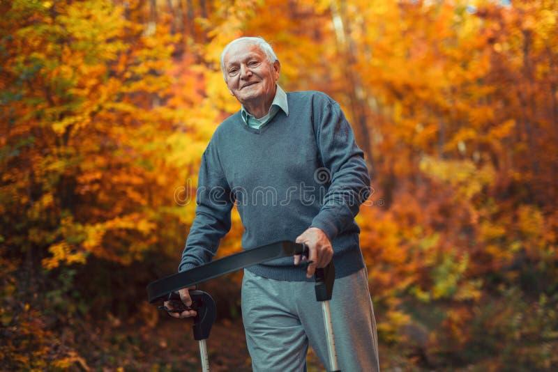 Glücklicher älterer Mann mit einem Gehen in Park lizenzfreie stockbilder