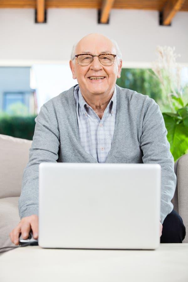 Glücklicher älterer Mann mit Laptop am Pflegeheim-Portal stockfoto