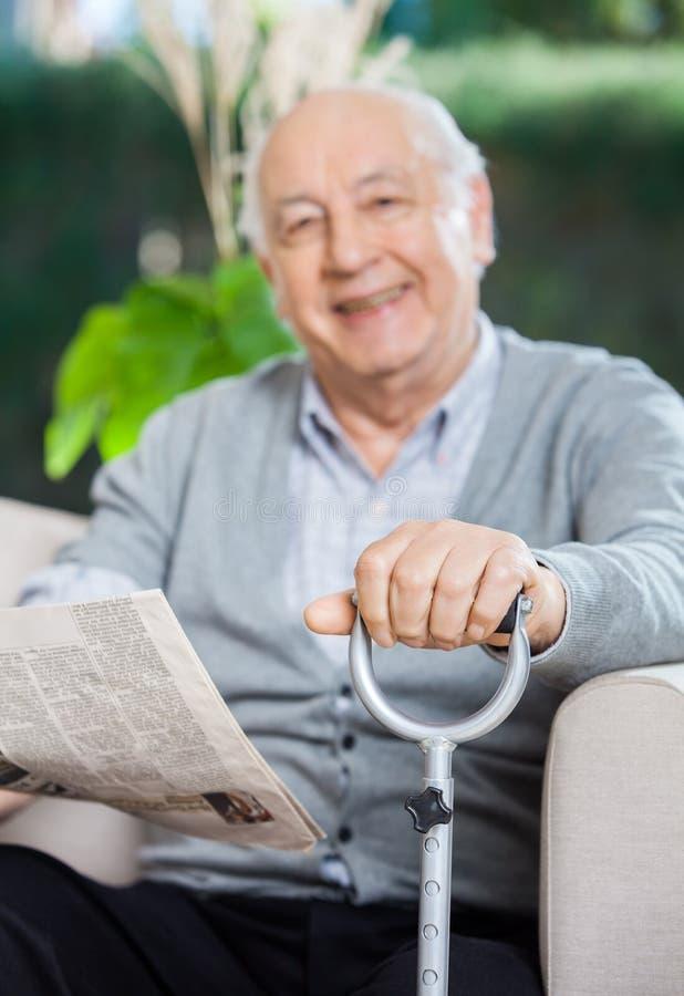 Glücklicher älterer Mann mit Zeitung und Cane Sitting lizenzfreies stockfoto