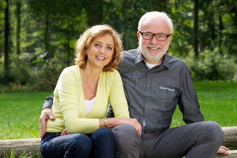 Glücklicher älterer Mann und Frau, die zusammen draußen sitzt stockbilder