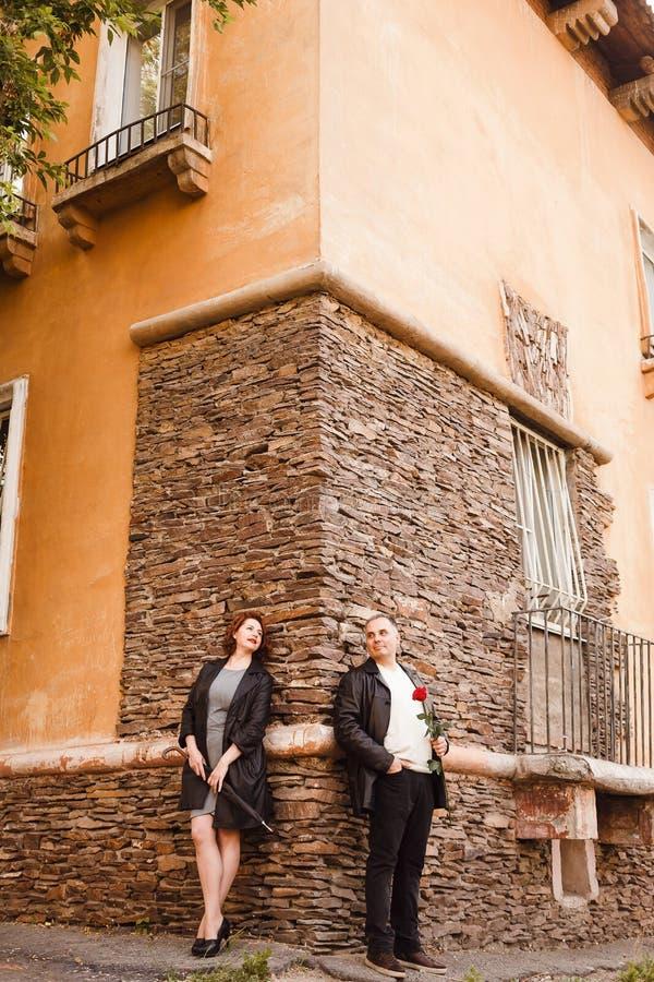 Gl?cklicher ?lterer Paarstand im vollen Wachstum nahe der Wand des Hauses im Sommer Ledermantel und Regenschirmstock lizenzfreie stockfotos