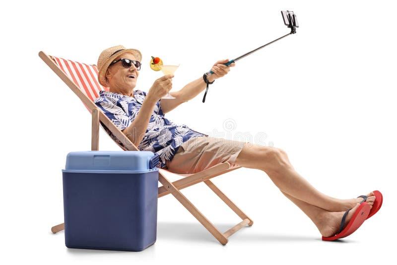 Glücklicher älterer Tourist mit einem Cocktail, das ein selfie lokalisiert nimmt stockfotografie