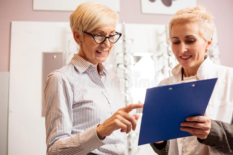 Glücklicher älterer weiblicher Patient, der mit reifem Optometriker sich berät lizenzfreie stockfotografie