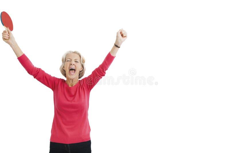Glücklicher älterer weiblicher Tischtennisspieler mit den Armen hob das Feiern des Sieges an stockbild