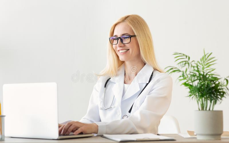 Glücklicher Ärztin-Working On Laptop-Computer lizenzfreie stockfotos