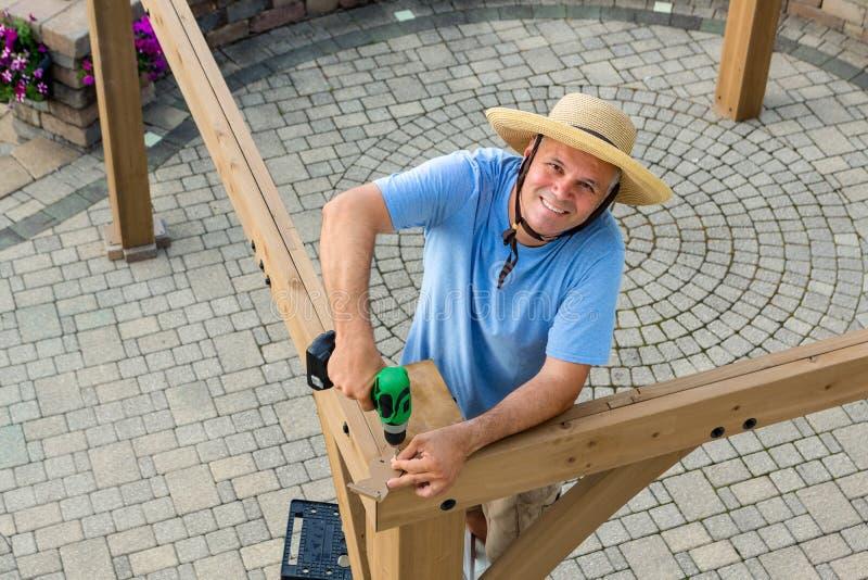 Glücklicher überzeugter Mann, der einen neuen Gazebo im Freien aufrichtet lizenzfreie stockbilder