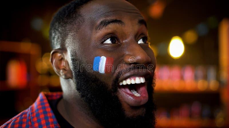 Glücklicher afrikanisch-mexikanischer Mann mit französischer Flagge auf Backe lächelnd, Lotterieergebnisse stockfotos