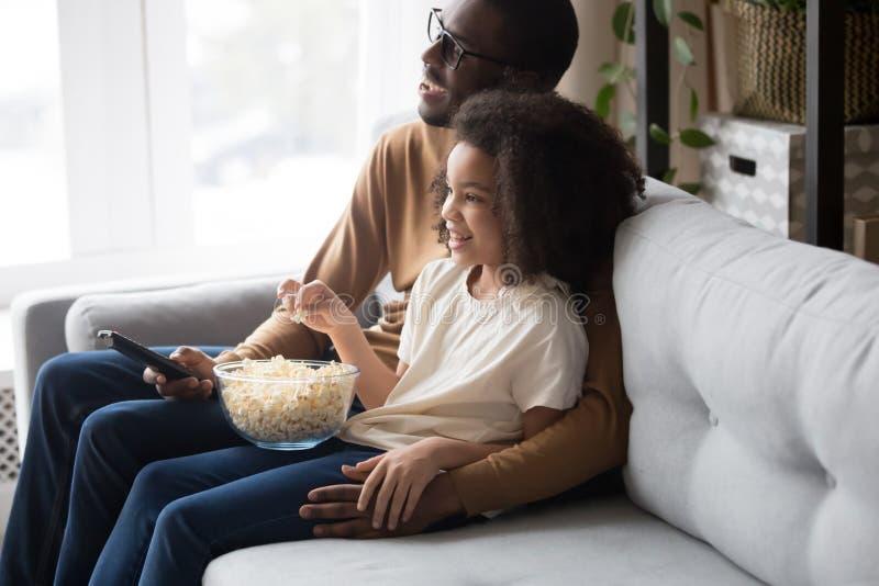 Glücklicher afrikanischer Familienvati mit der Kindertochter, die zusammen fernsieht lizenzfreies stockbild