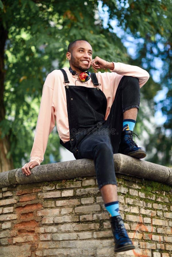 Glücklicher afrikanischer Kerl mit Schellfischhosen draußen lizenzfreie stockfotografie