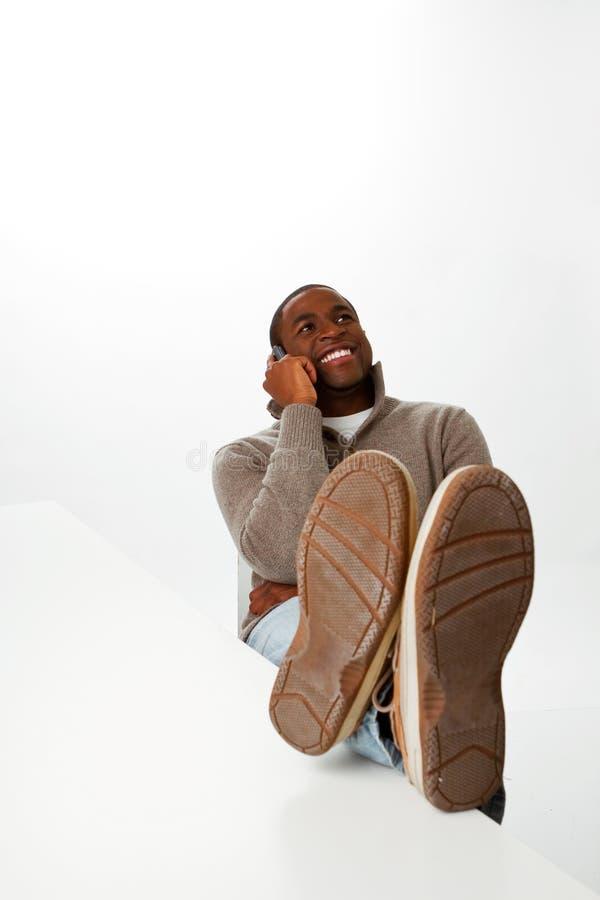 Glücklicher afrikanischer Mann, der mit seinen Armen gekreuzt sitzt stockbilder