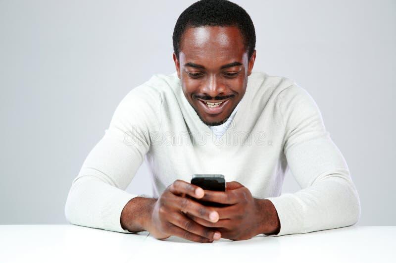 Glücklicher afrikanischer Mann, der am Tisch sitzt lizenzfreies stockbild